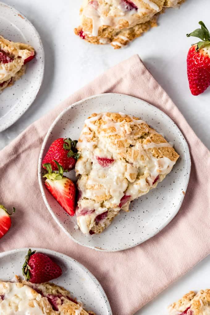 A glazed strawberry scone on a plate set on a pink napkin