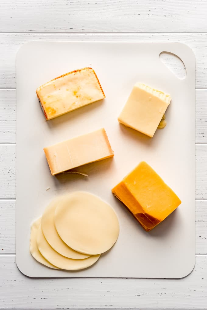 five different types of cheese on a white cutting board
