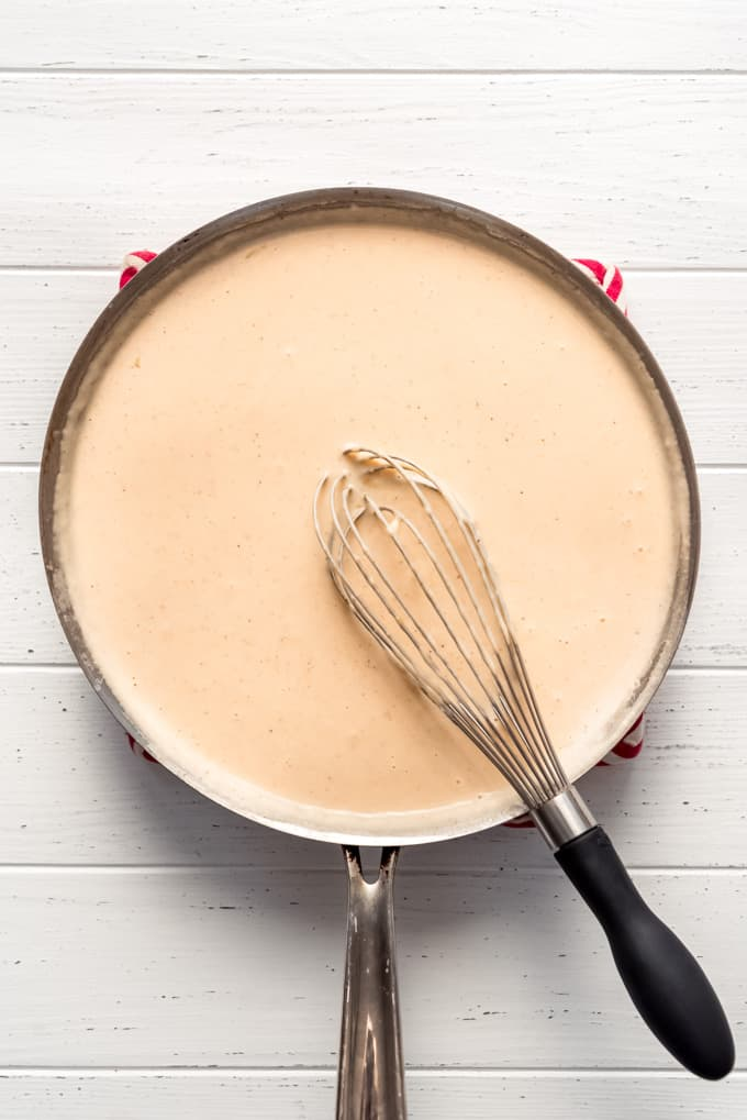 a homemade cheesy sauce in a large pan with a whisk in it