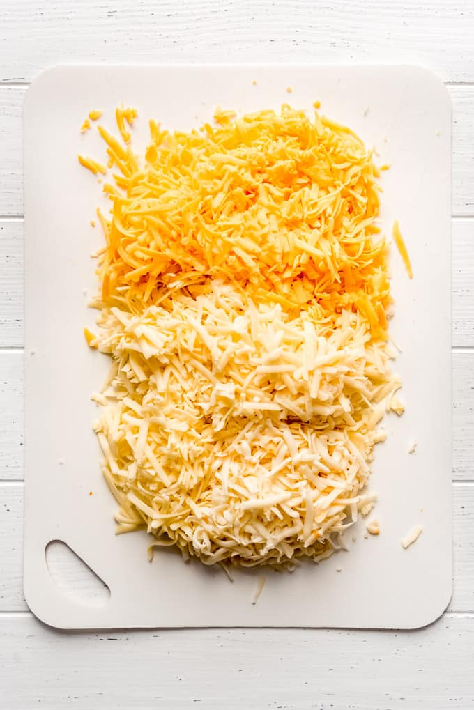 different types of grated cheese on a cutting board