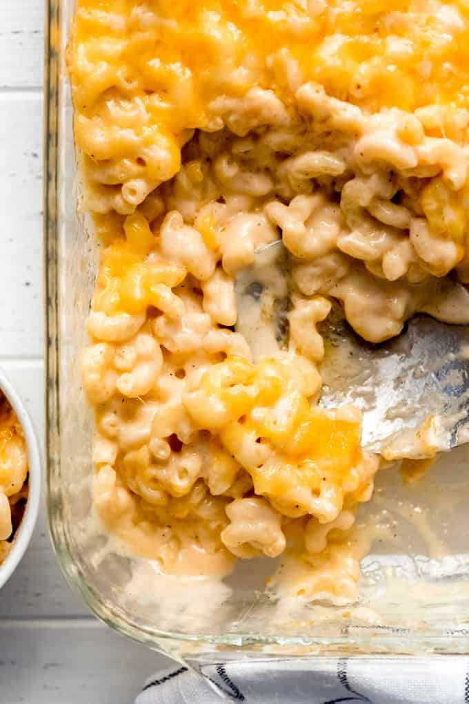 macaroni and cheese being scooped out of a casserole dish