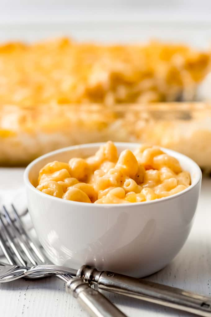 a bowl of homemade mac and cheese in front of a casserole dish