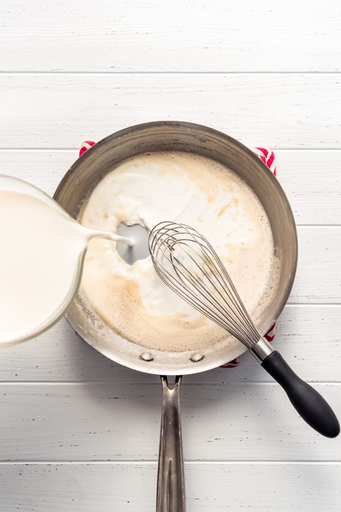 pouring milk into a large pan with roux