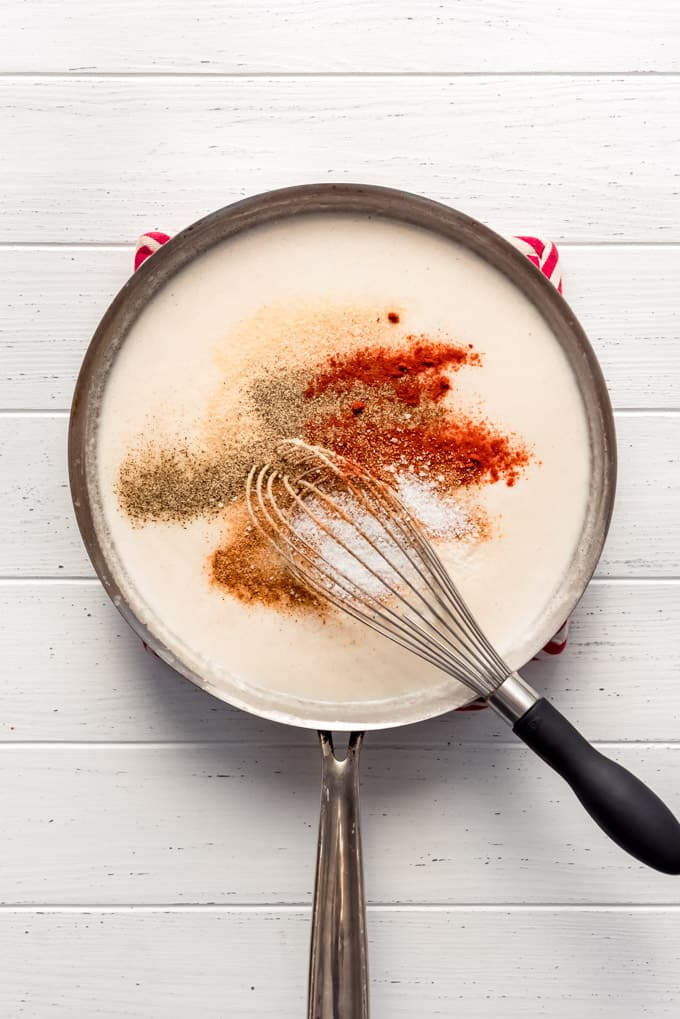 adding spices and seasoning to a creamy sauce