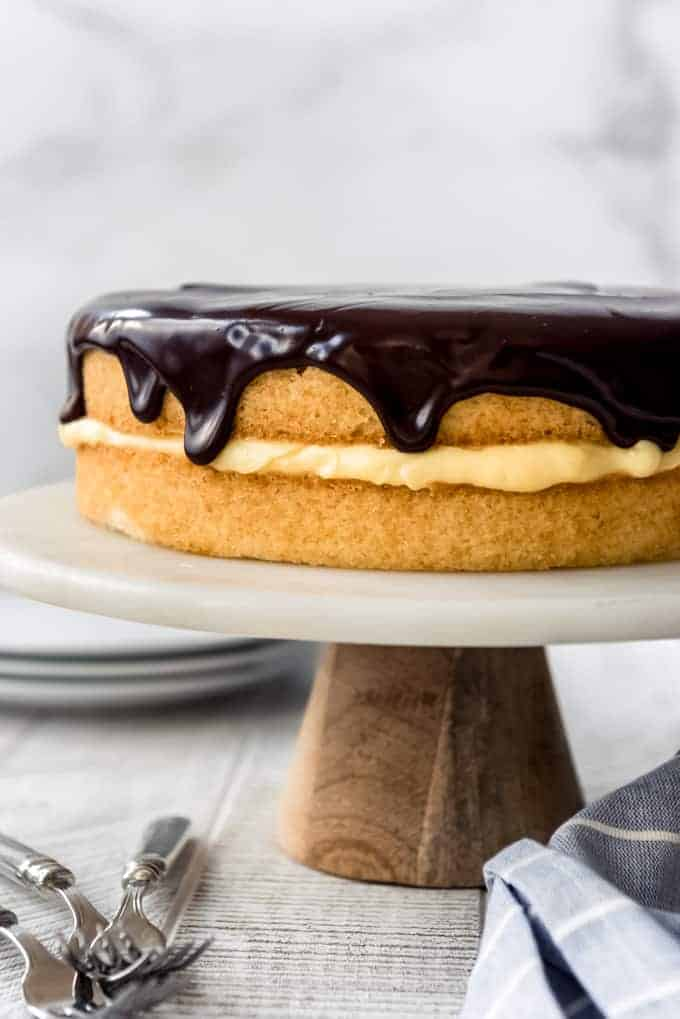 a close image of chocolate ganache dripping down the side of a boston cream pie