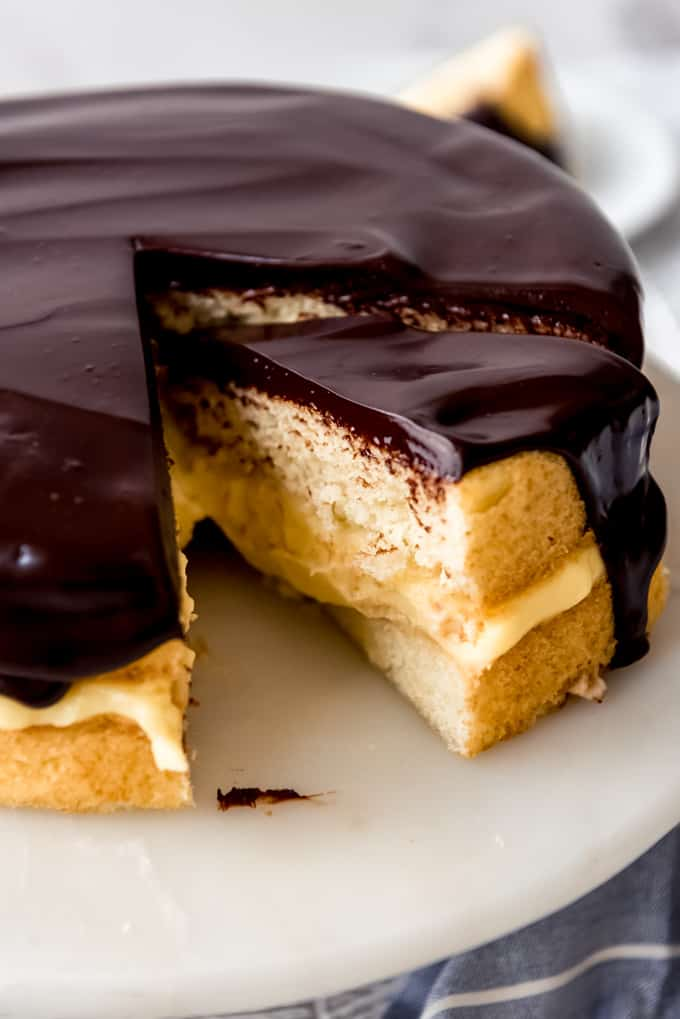 a slice of boston cream pie being removed from the cake stand