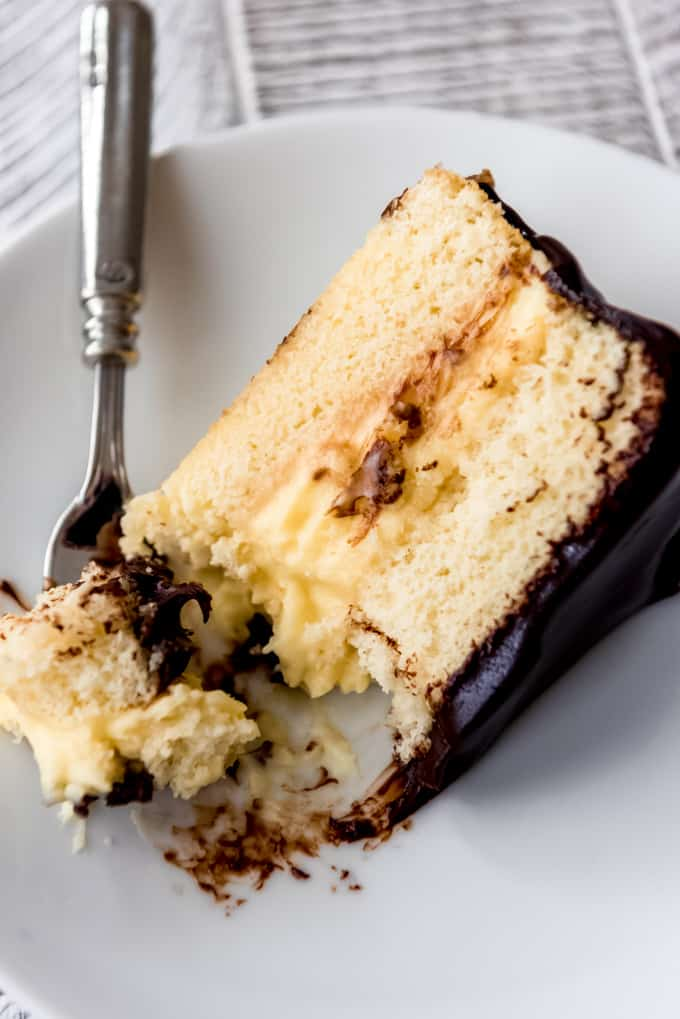 a slice of boston cream pie with a bite on a fork beside it