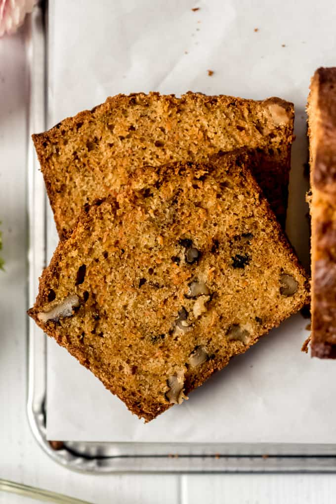 a close image of two slices of carrot bread studded with walnuts