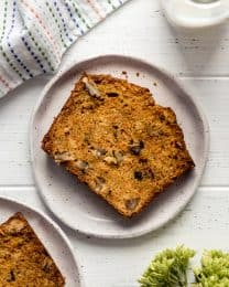 a piece of carrot bread with walnuts on a plate
