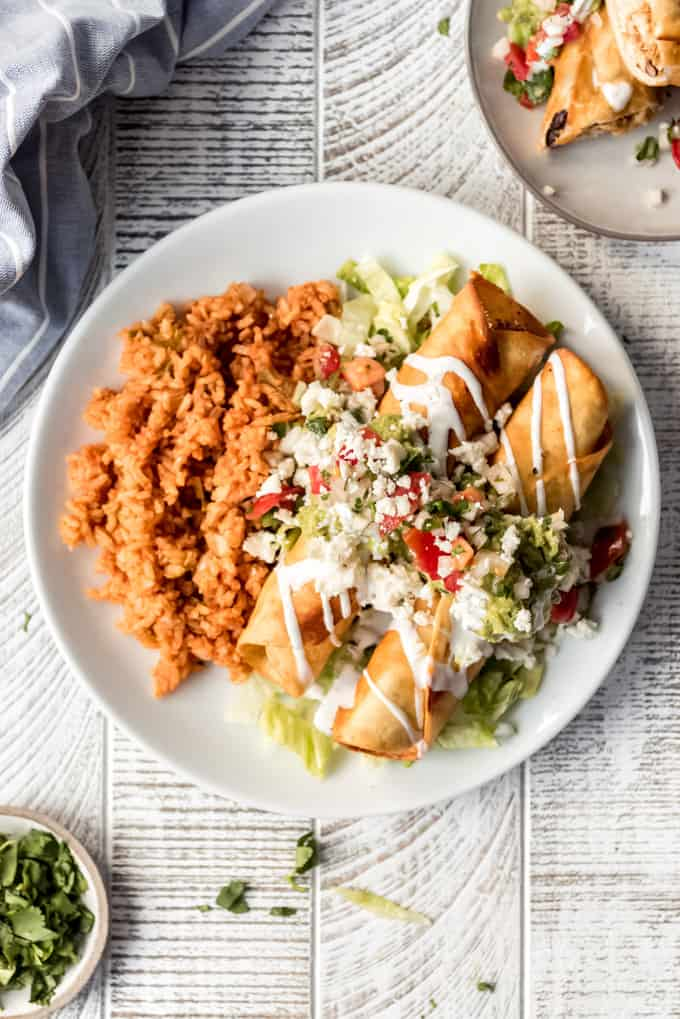 a white plate with Mexican rice and chicken flautas