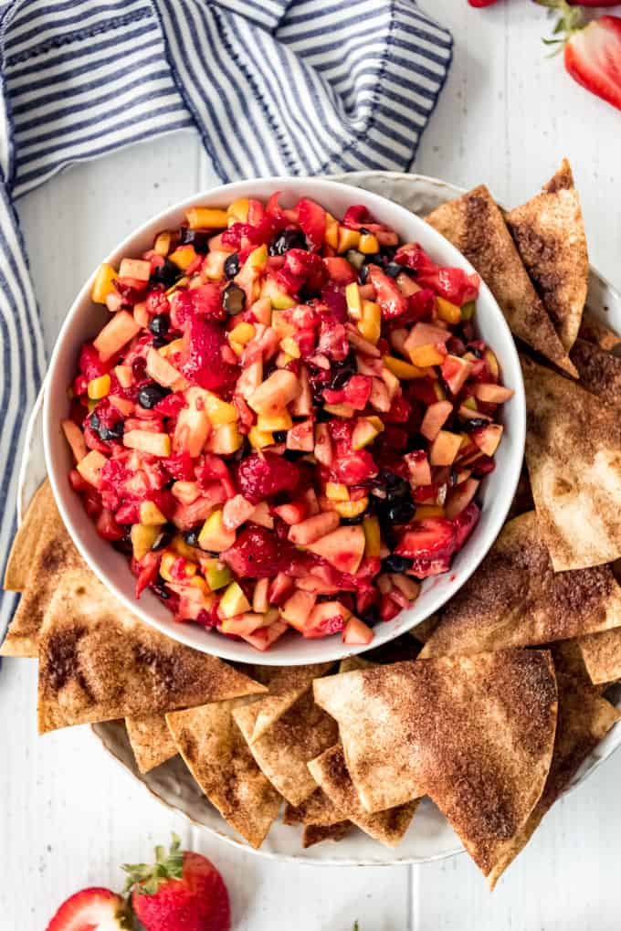 a bowl of fresh fruit salsa with cinnamon sugar tortilla chips on the side