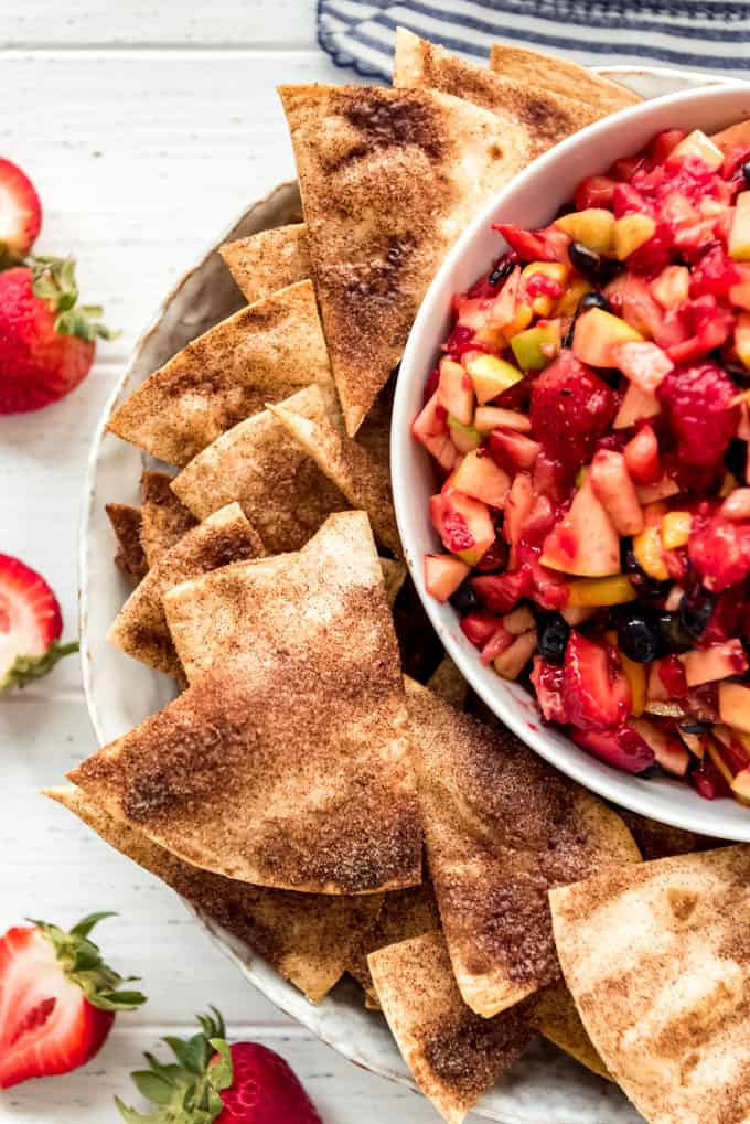 cinnamon sugar tortilla chips on a plate next to fruit salsa in a bowl