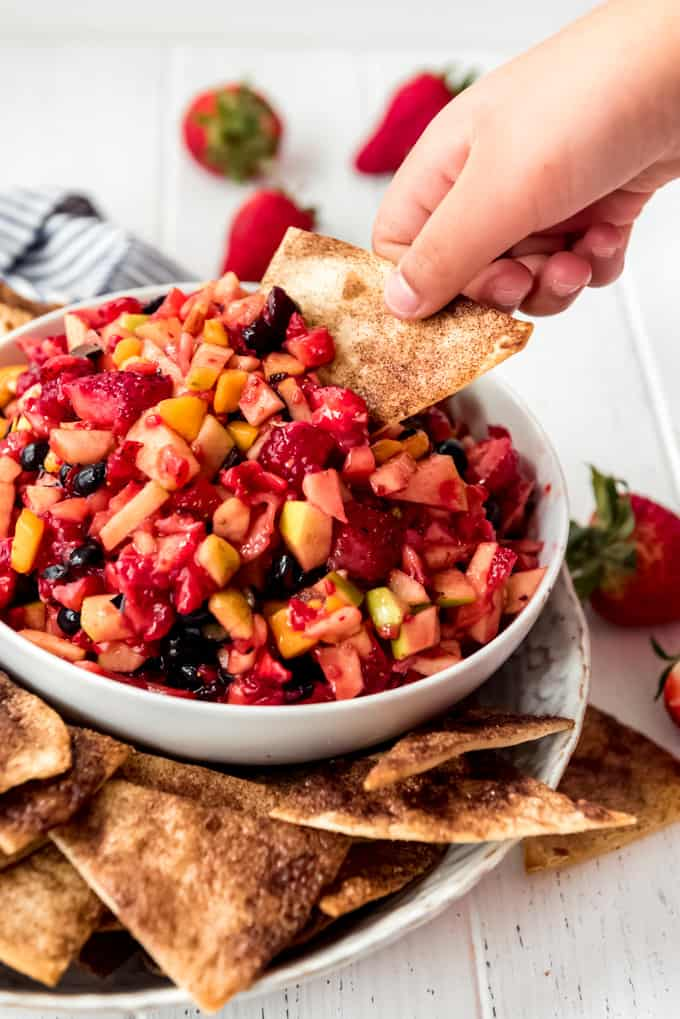 a hand holding a cinnamon chip to scoop fruit salsa out of a bowl