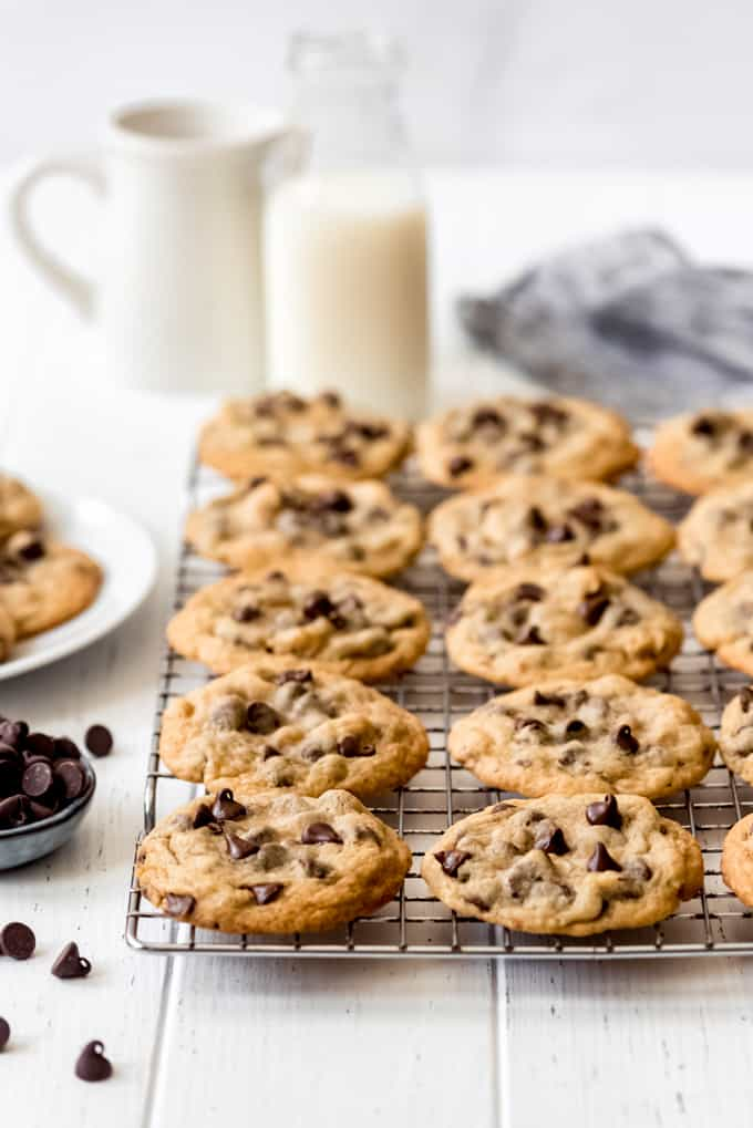 chocolate chip cookies on a wire rack in front of a bottle of milk