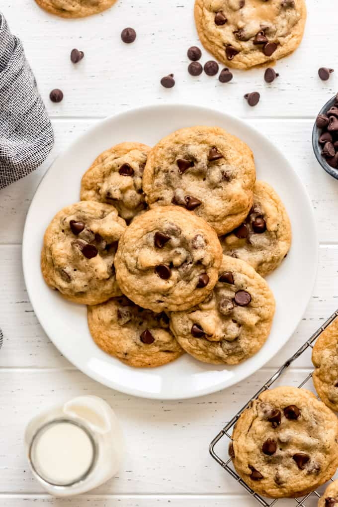 a white plate with chocolate chip cookies and more chocolate chips and cookies around it