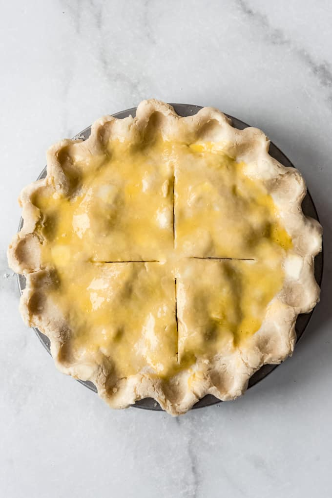 unbaked rhubarb pie with crimped edged, slits for venting, and an egg wash brushed on top