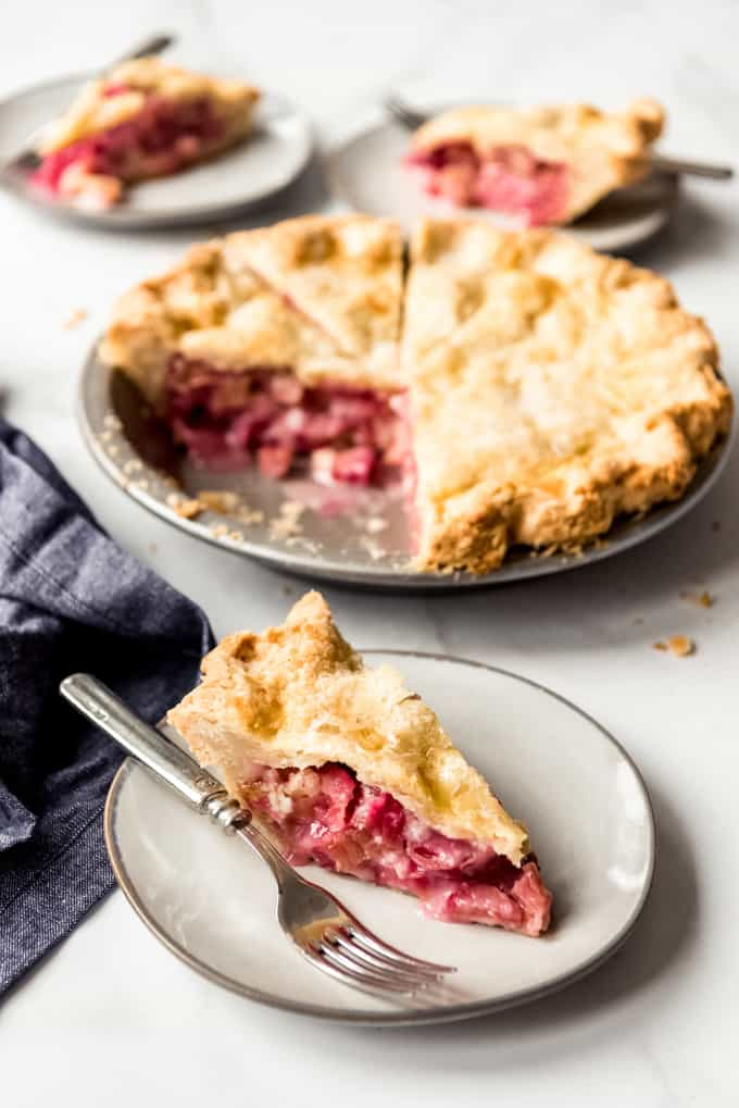 A slice of rhubarb pie cut on place with a fork and the whole baked rhubarb pie in pie pan with slice cut out