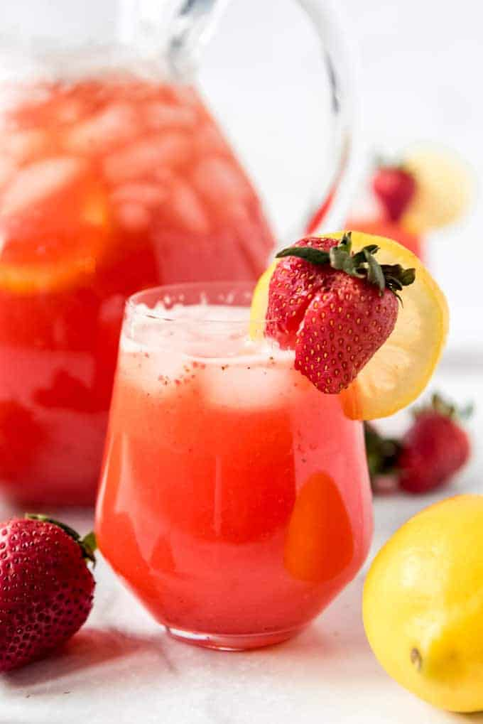 a glass of fresh homemade strawberry lemonade with a lemon wedge and strawberry garnish
