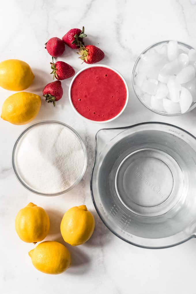 whole lemons, whole strawberries, mashed strawberries in a bowl, a bowl of ice, a bowl of sugar, a bowl of water on a white table