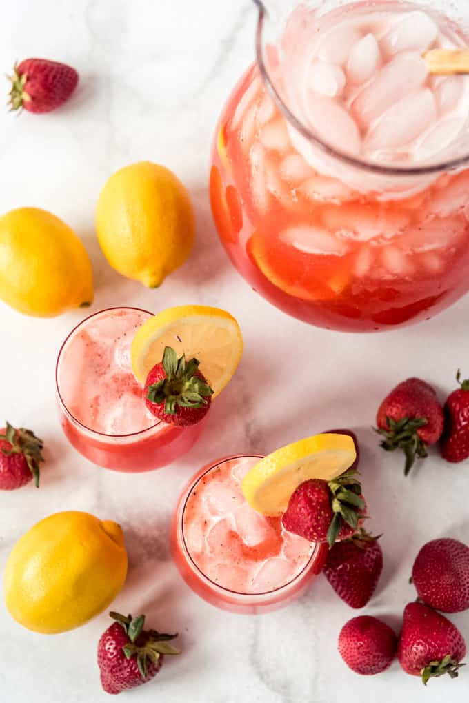 two glasses of strawberry lemonade and ice with a lemon wedge and strawberry on the rim as garnish and whole fresh strawberries on a white table top