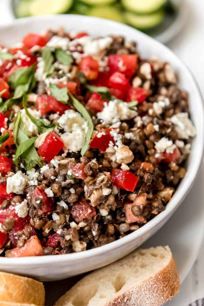 a close image of lentils, tomatoes, basil, feta cheese, and olive oil in a bowl