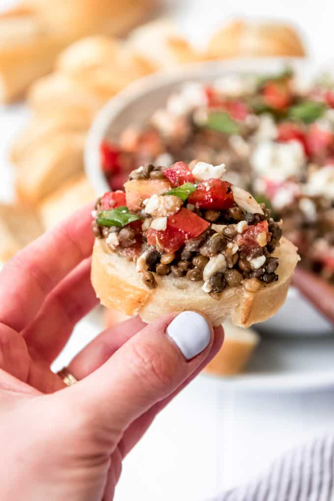 a hand holding a piece of baguette topped with lentil bruschetta feta dip