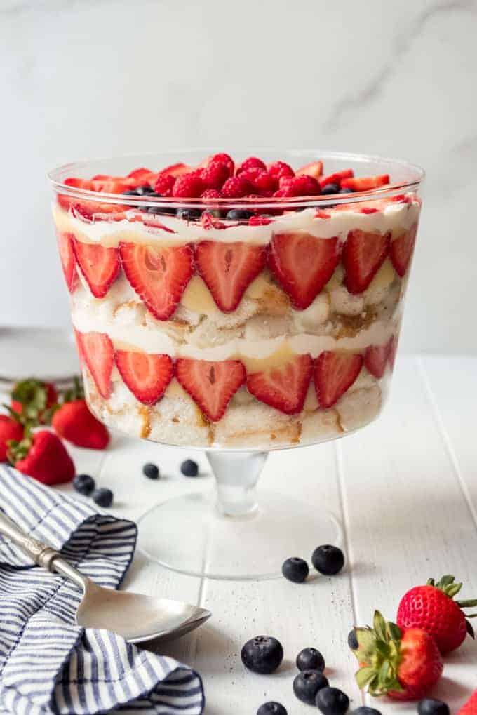 layers of angel food cake, pudding, whipped cream, and strawberries in a glass trifle dish