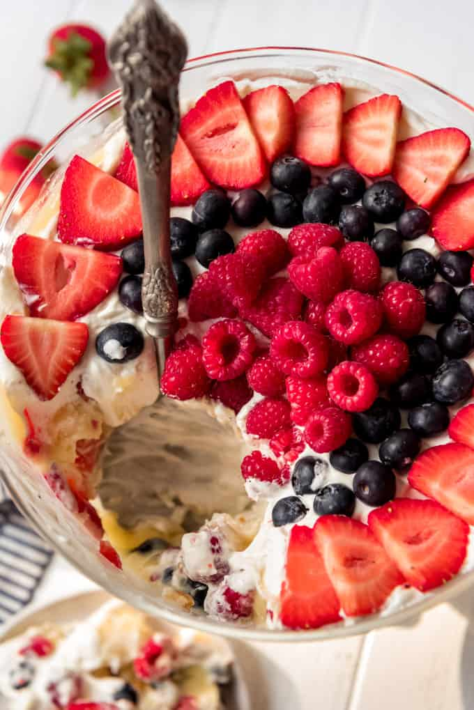 a serving spoon scooping out fruit trifle from a bowl