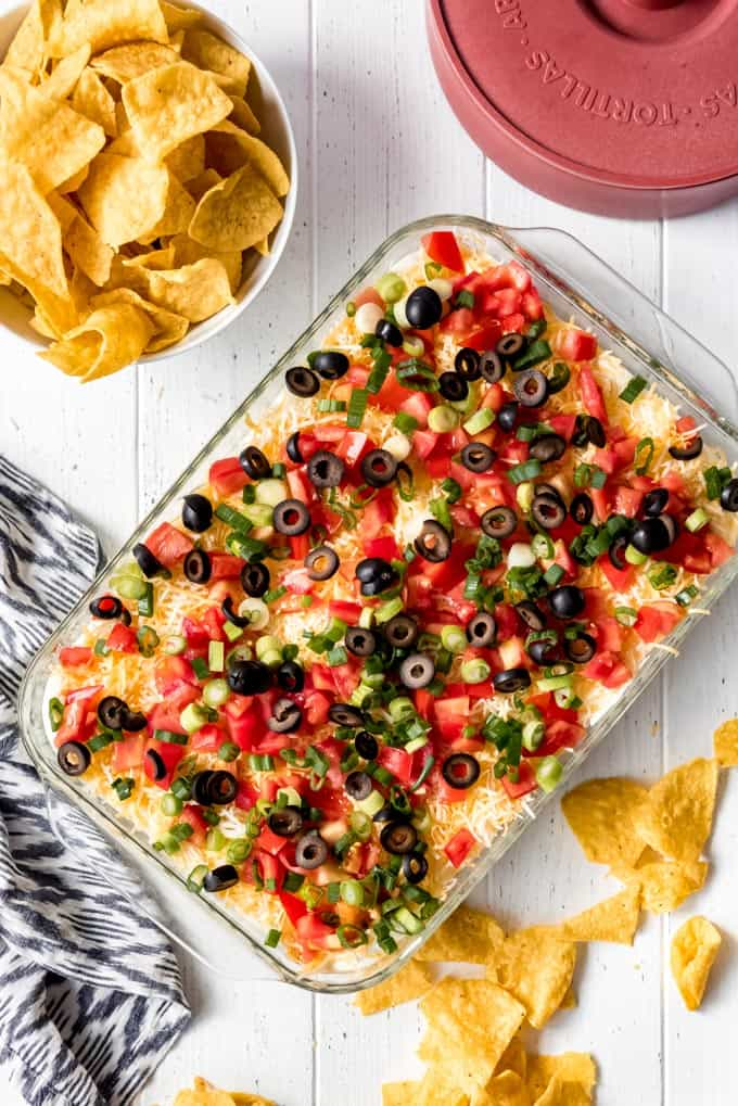 A 9x13 pan of 7 layer dip with a side of chips and a container of tortillas