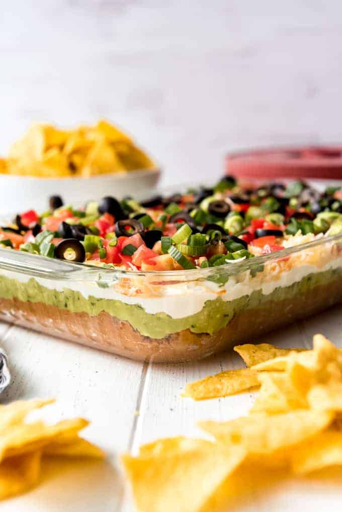 7 layer dip in a 9x13 glass dish with a side of chips