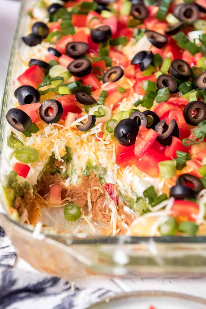a spoonful of 7 layer dip taken out of a 9x13 glass dish