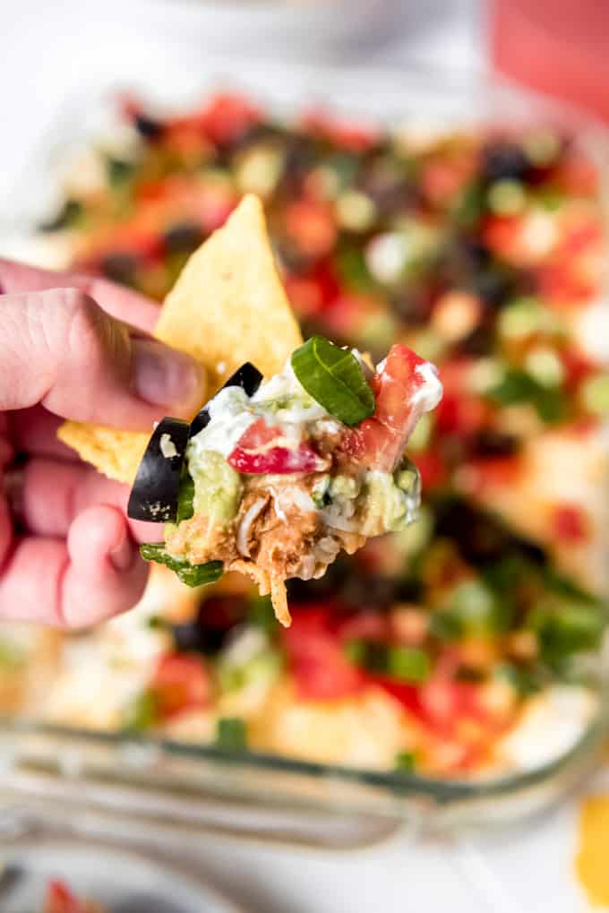 a scoop of 7 layer dip on a tortilla chip