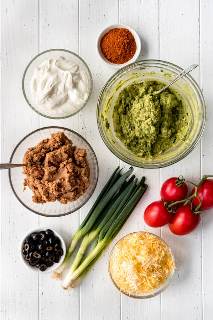 Ingredients for 7 layer dip. A bowl of taco seasoning, sour cream, refried beans, guacamole, olives, shredded cheese, fresh green onions and tomatoes