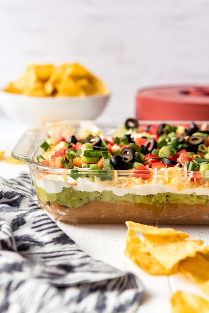 a side view of 7 layer dips in a glass serving dish