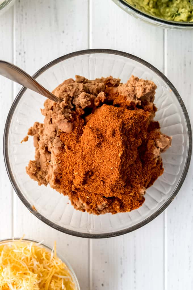 a glass bowl of refried beans with taco seasoning on top