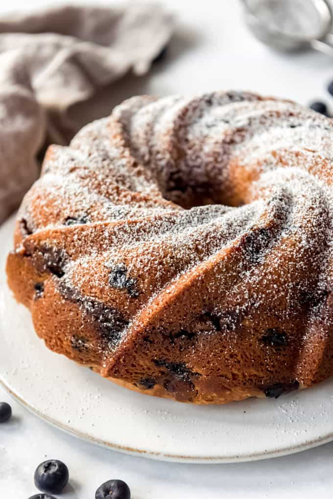 Blueberry Sour Cream Coffee Cake on a white serving dish sprinkled with powdered sugar.