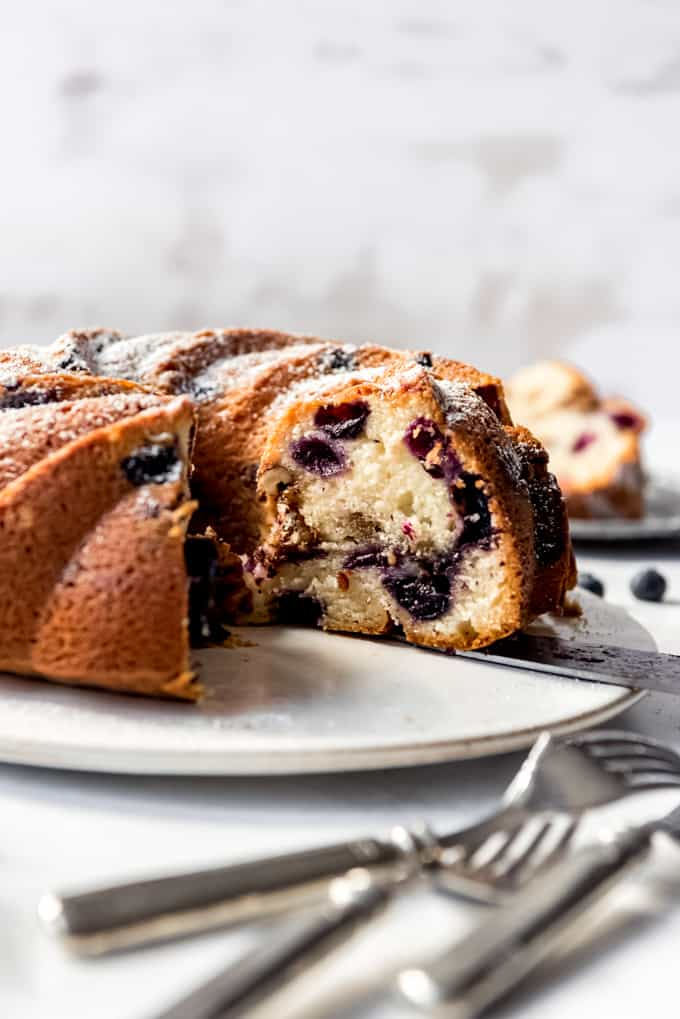 Blueberry Sour Cream Coffee Cake on a white cake tray with pieces cut out