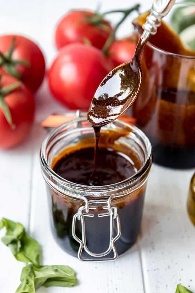 a spoon drizzling balsamic glaze into a jar