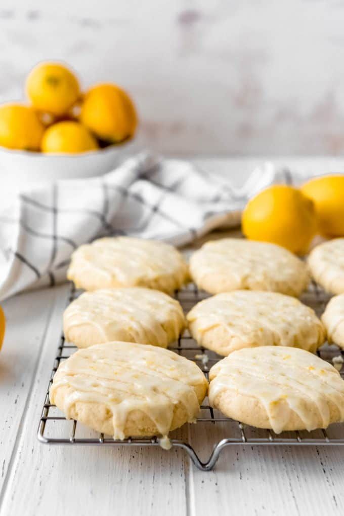 lemon sugar cookies on a wire rack with glaze on top of them next to a bowl of lemons