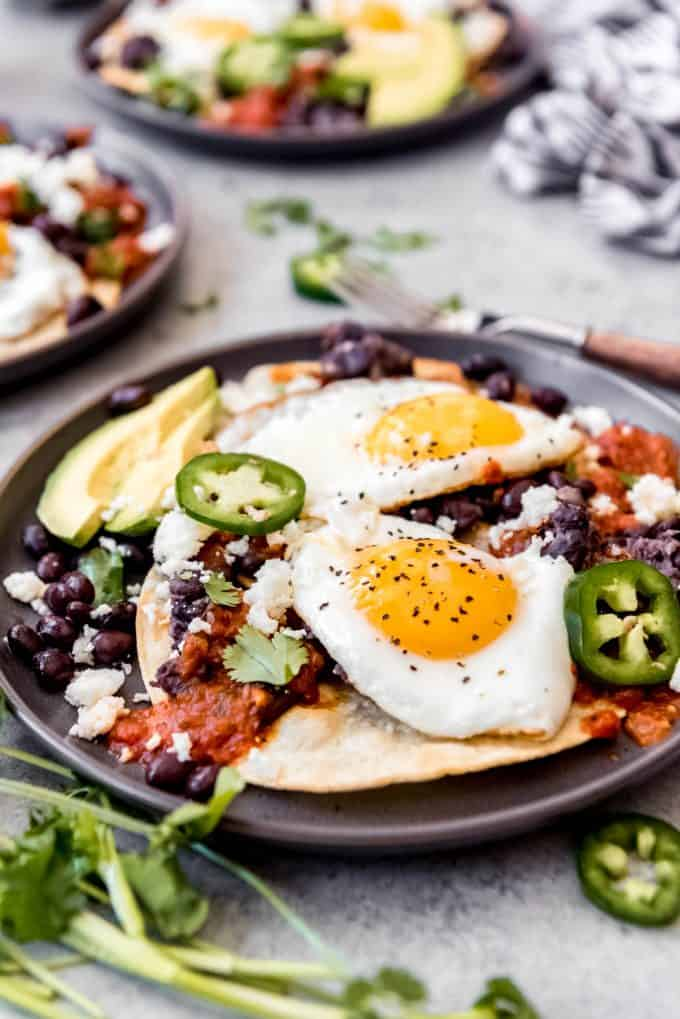 two huevos rancheros on a plate topped with jalapenos and cheese