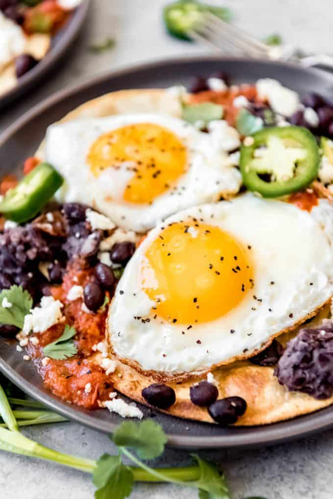 two fried eggs, on top of a bed of beans and ranchero sauce, atop of crispy tortillas