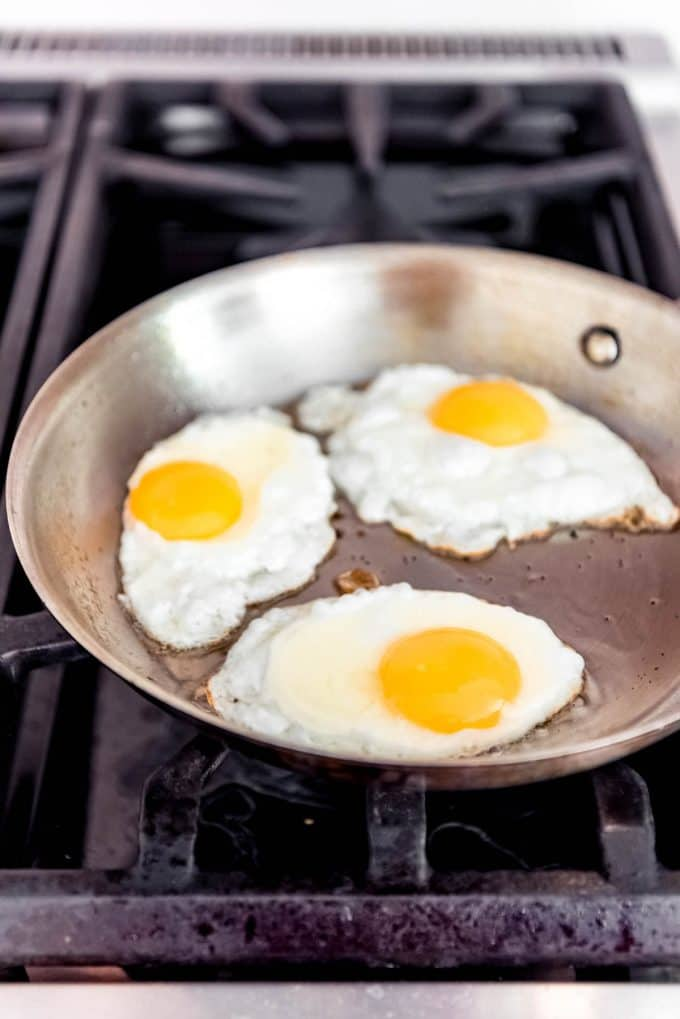 three eggs frying in a pan on the stove