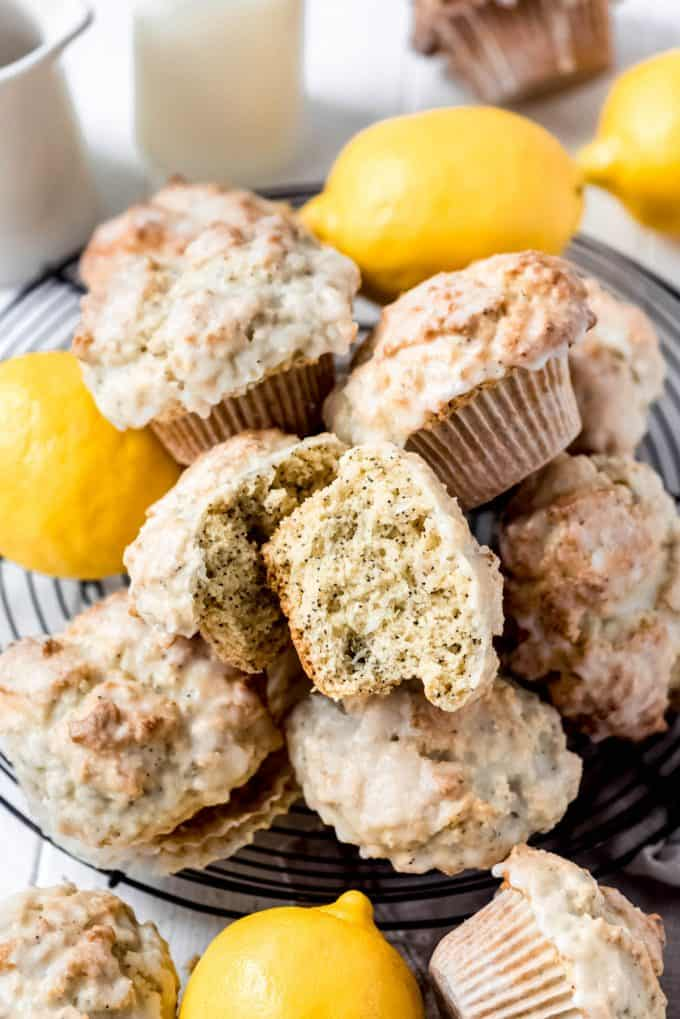 a lemon poppy seed muffin split open on top of a pile of more muffins and lemons