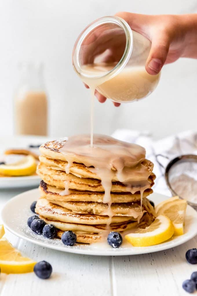 a stack of pancakes with coconut syrup being poured on top