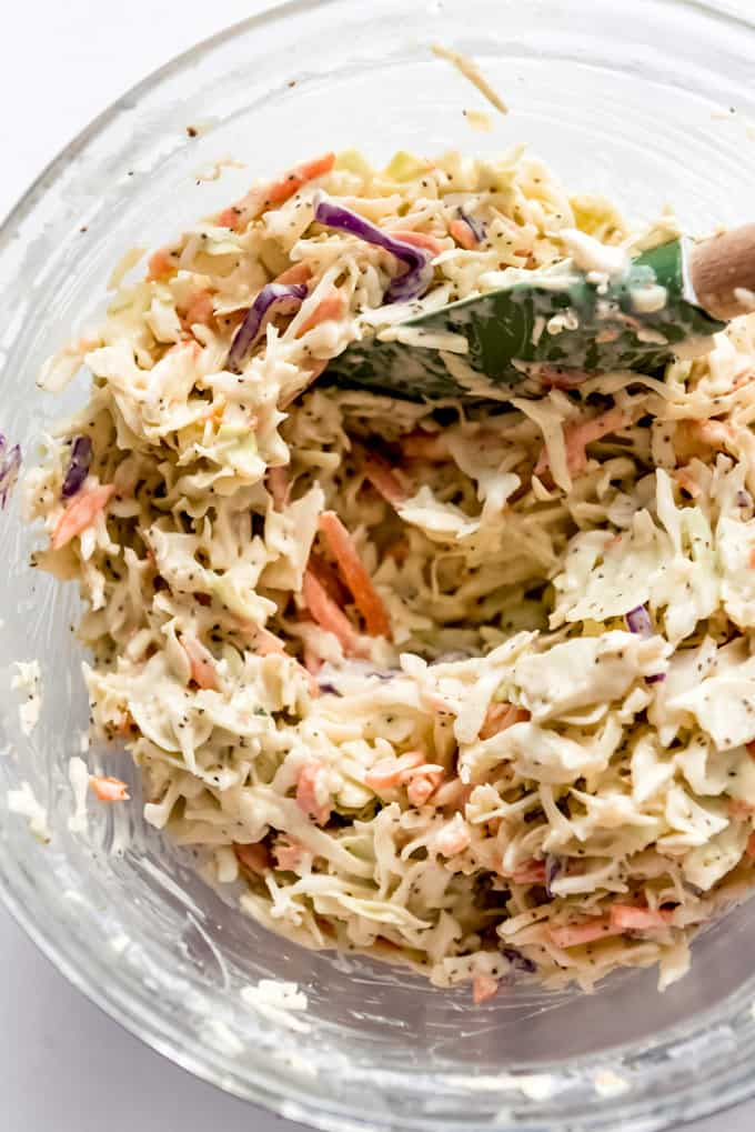 stirring coleslaw dressing into shredded cabbage and carrots