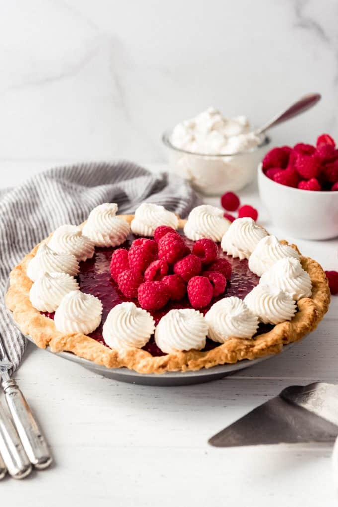 a raspberry pie topped with whipped cream in front of bowls of whipped cream and raspberries
