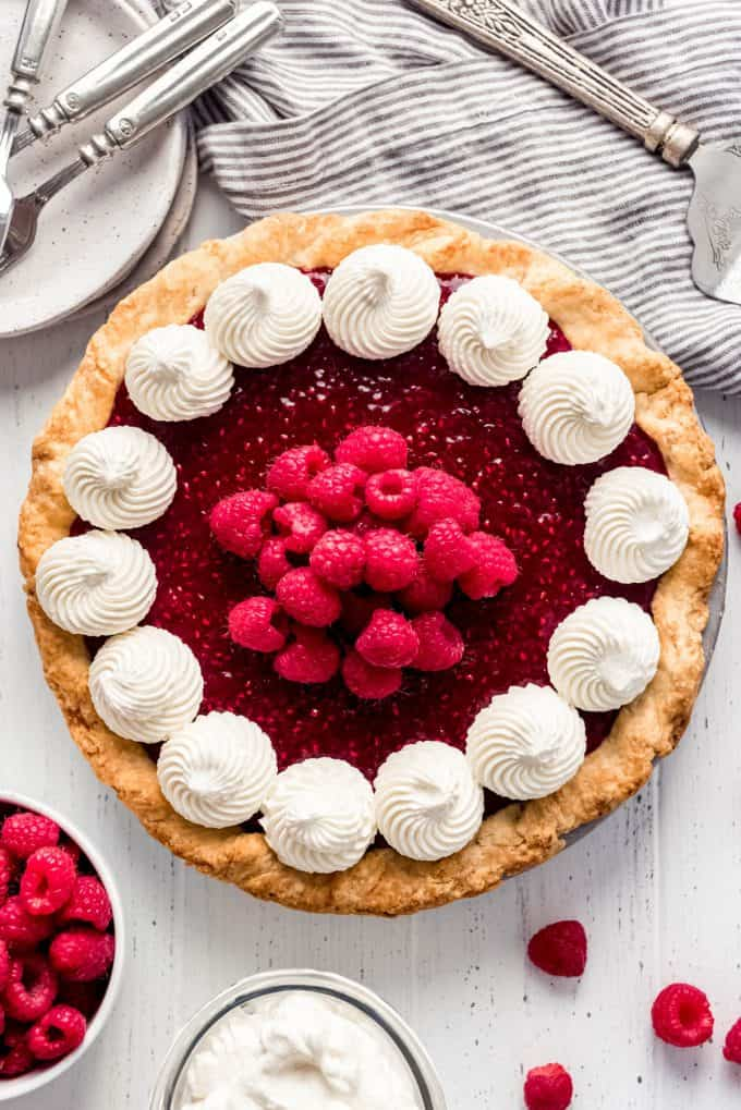 a raspberry cream pie topped with swirls of whipped cream and fresh raspberries