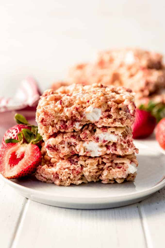 Strawberry Rice Krispies Treats stacked on a white plate served with fresh strawberries