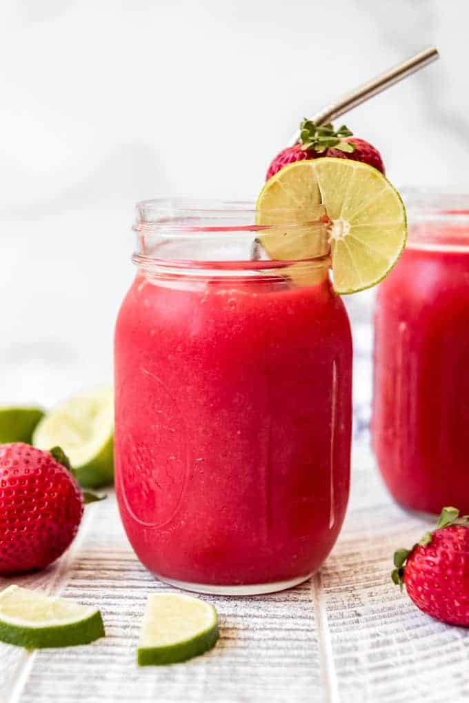 a glass mason jar full of frozen virgin strawberry daiquiri