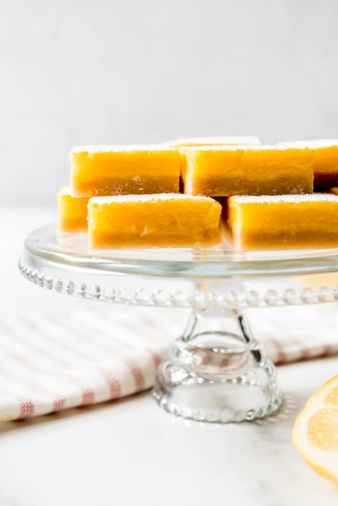 lemon squares stacked on a glass cake stand